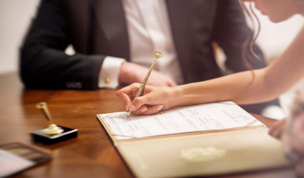 Para młoda podpisująca dokumenty do ślubu
