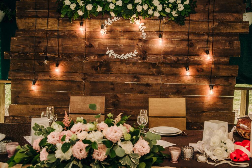 Rustykalna ścianka weselna za parą młodą