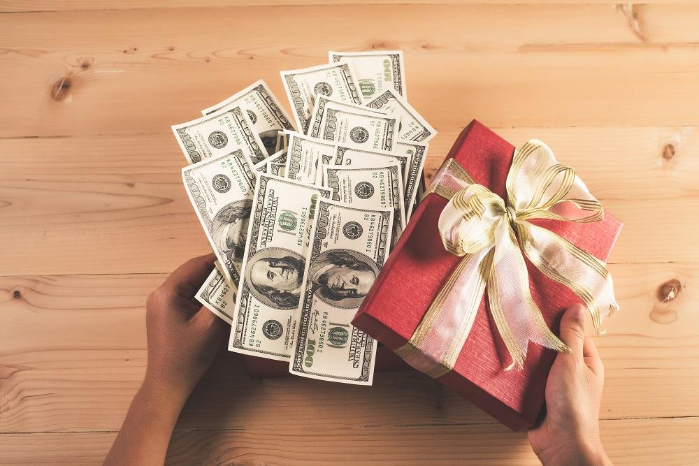 Jak zapakować pieniądze na prezent. Banknoty w czerwonym ozdobnym pudełku.