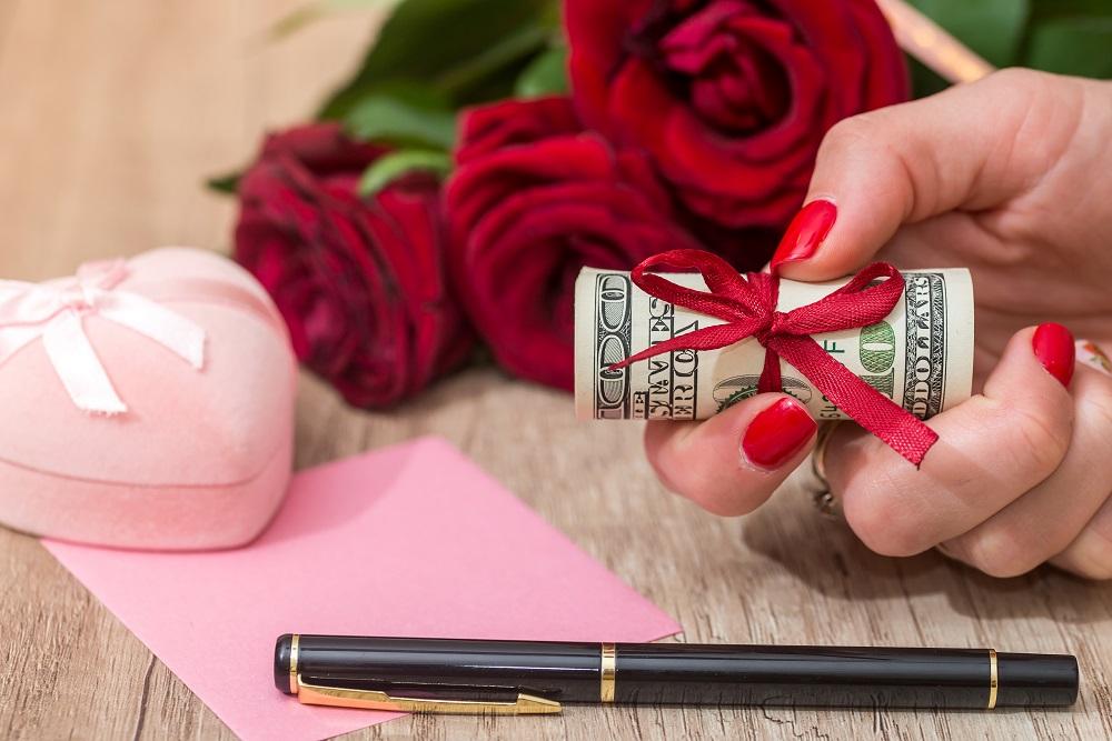 Jak zapakować pieniądze na prezent. Kobieta trzyma rolkę banknotów owiniętych czerwoną wstążką.
