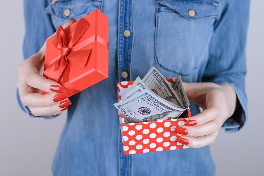 Jak zapakować pieniądze na prezent. Kobieta w niebieskiej koszuli trzyma pudełko z banknotami.