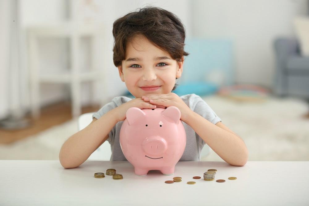 Jak zapakować pieniądze na prezent. Mały chłopczyk ze świnką skarbonką