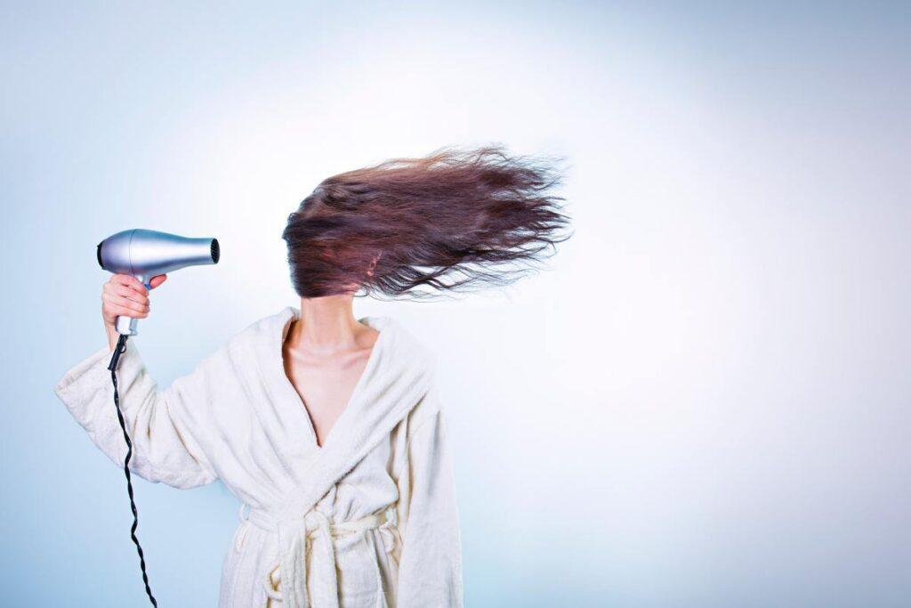 Kobieta suszy włosy i walczy z bad hair day