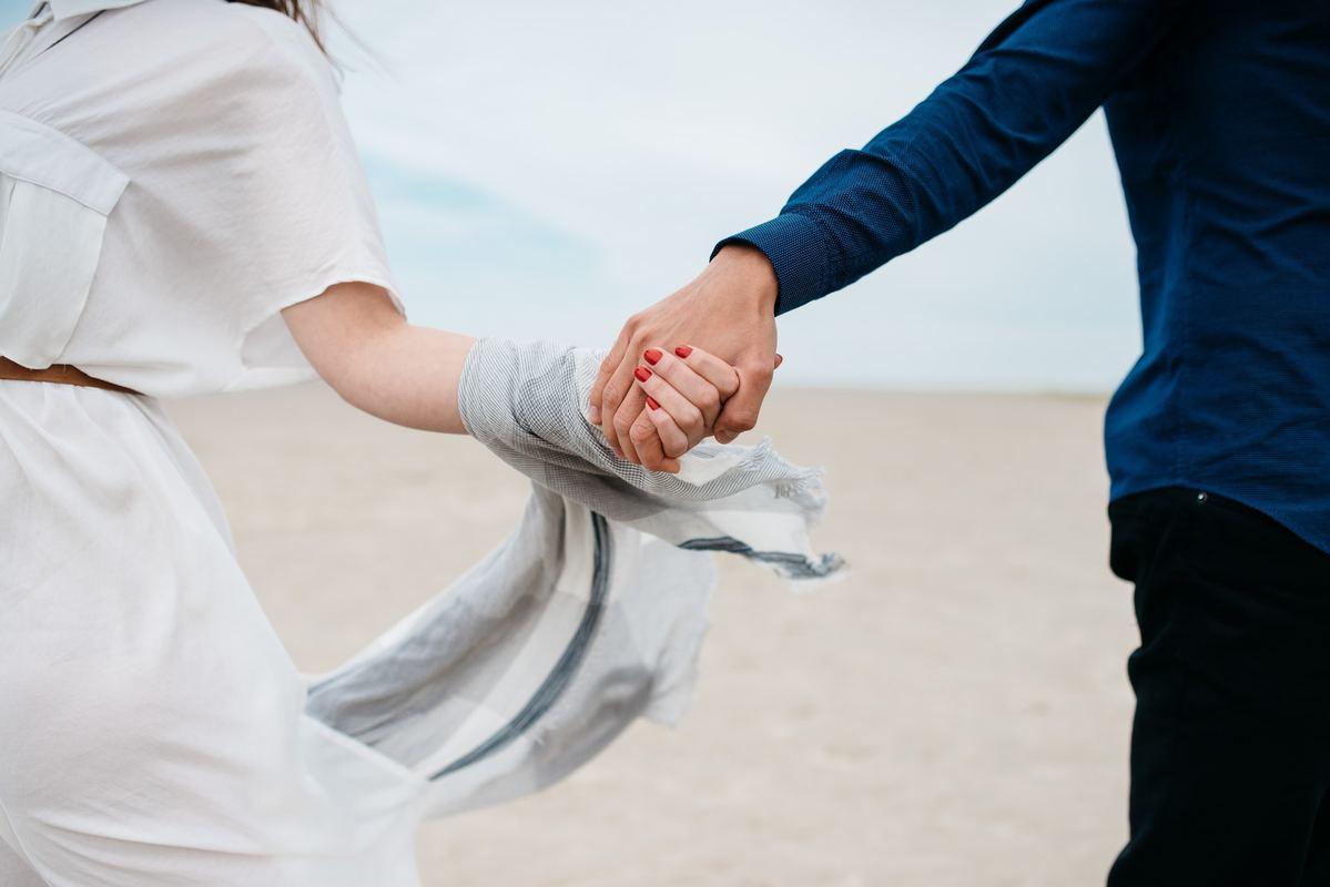 Zakochana para na plaży trzyma się za ręce