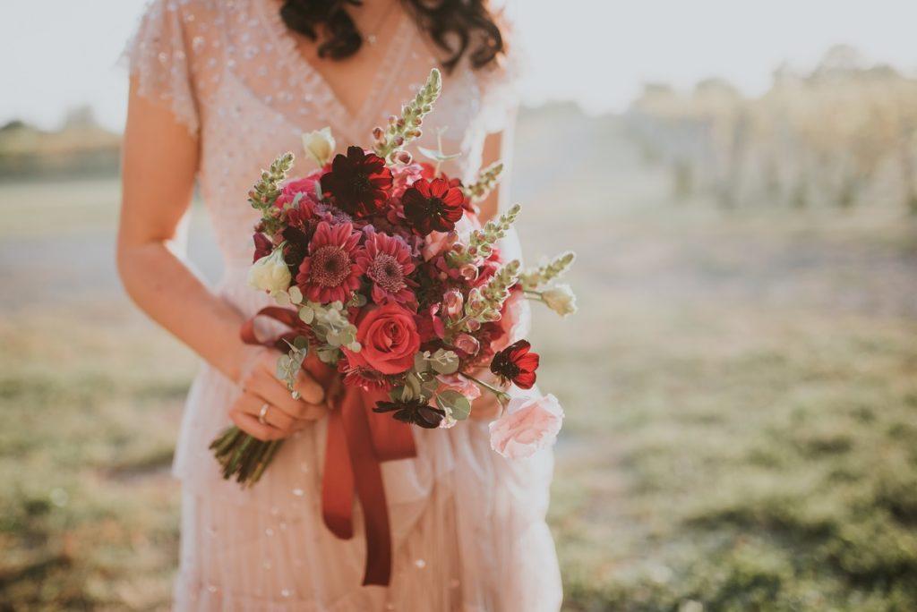 Różowa suknia ślubna. Panna młoda w delikatnej sukni ślubnej z bukietem.