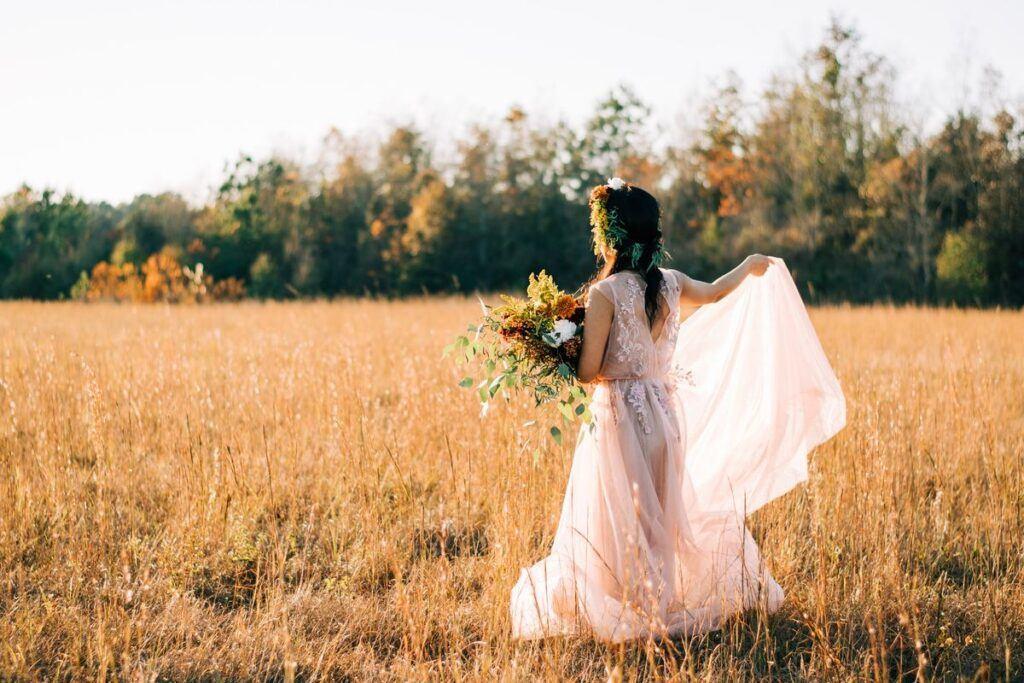 Różowa suknia ślubna. Panna młoda w różowej sukni na łące.
