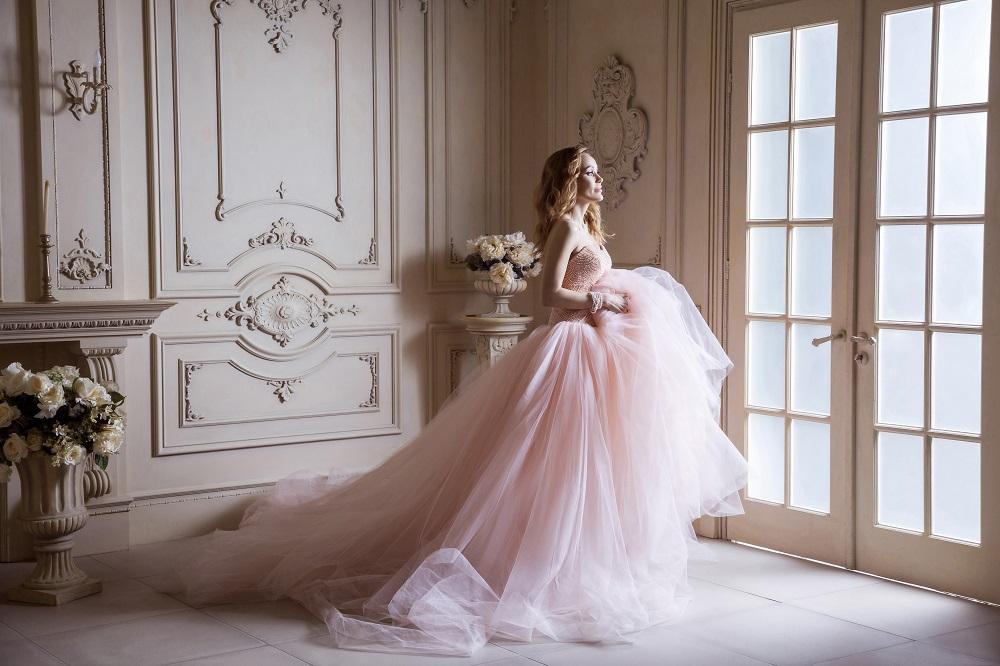 Różowa suknia ślubna. Panna młoda w pięknej różowej sukni w pałacu.