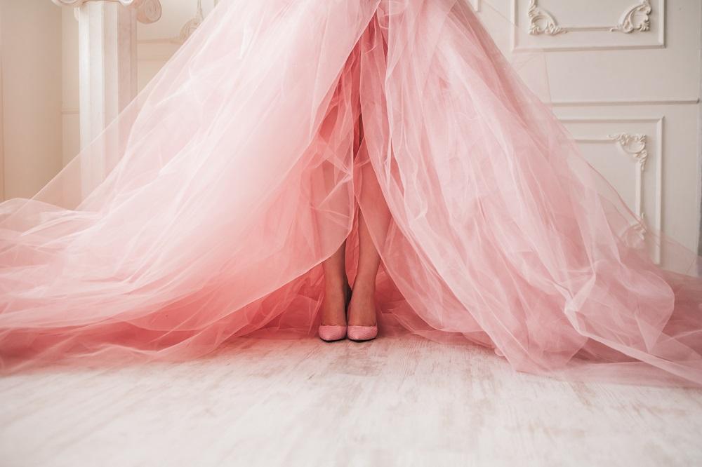 Różowa suknia ślubna. Nogi panny młodej w różowej sukni.