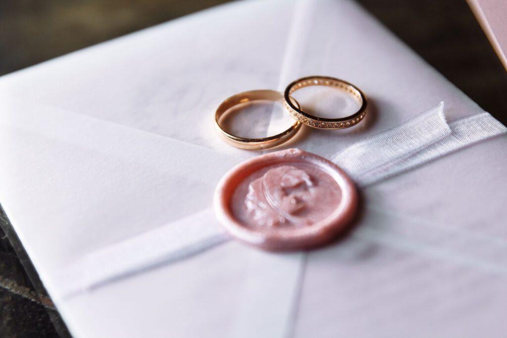 Nietypowe obrączki ślubne leżące na zaproszeniu