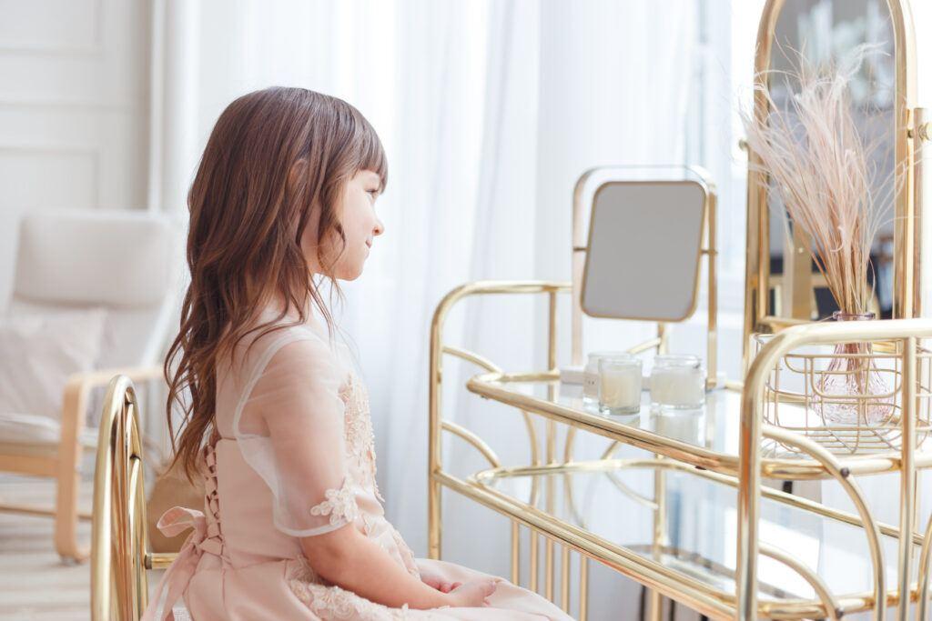 dziewczynka w eleganckiej sukience przegląda się w lustrze