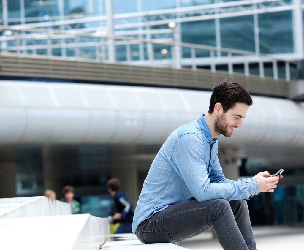 mężczyzna siedzi na schodach, korzysta z telefonu i uśmiecha się