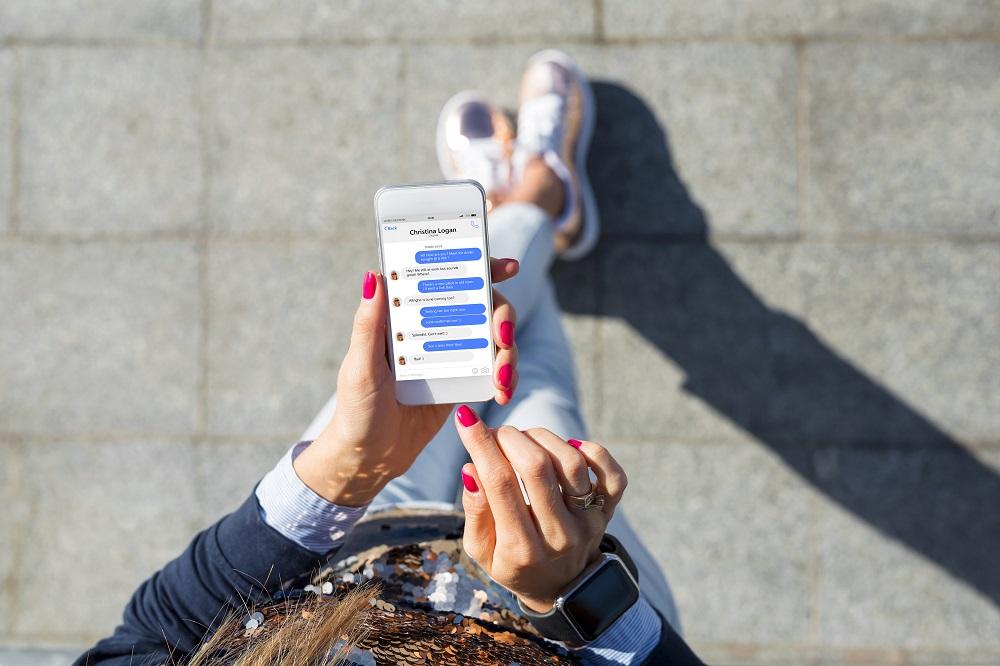 Jak pisać z dziewczyną. Dziewczyna siedzi na ulicy i pisze wiadomości przez telefon.