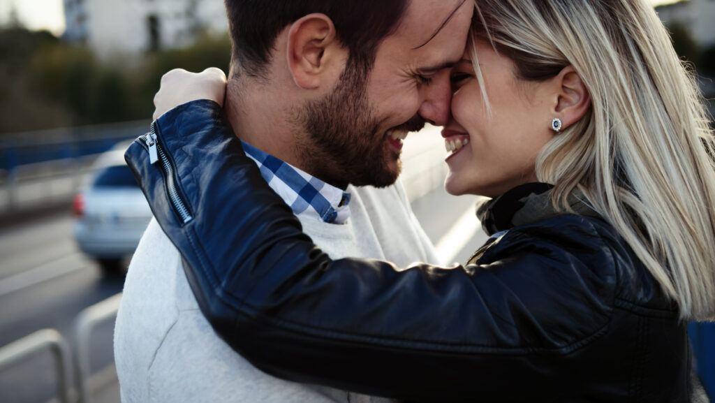 Szczęśliwa i uśmiechnięta para przytulająca się i całująca