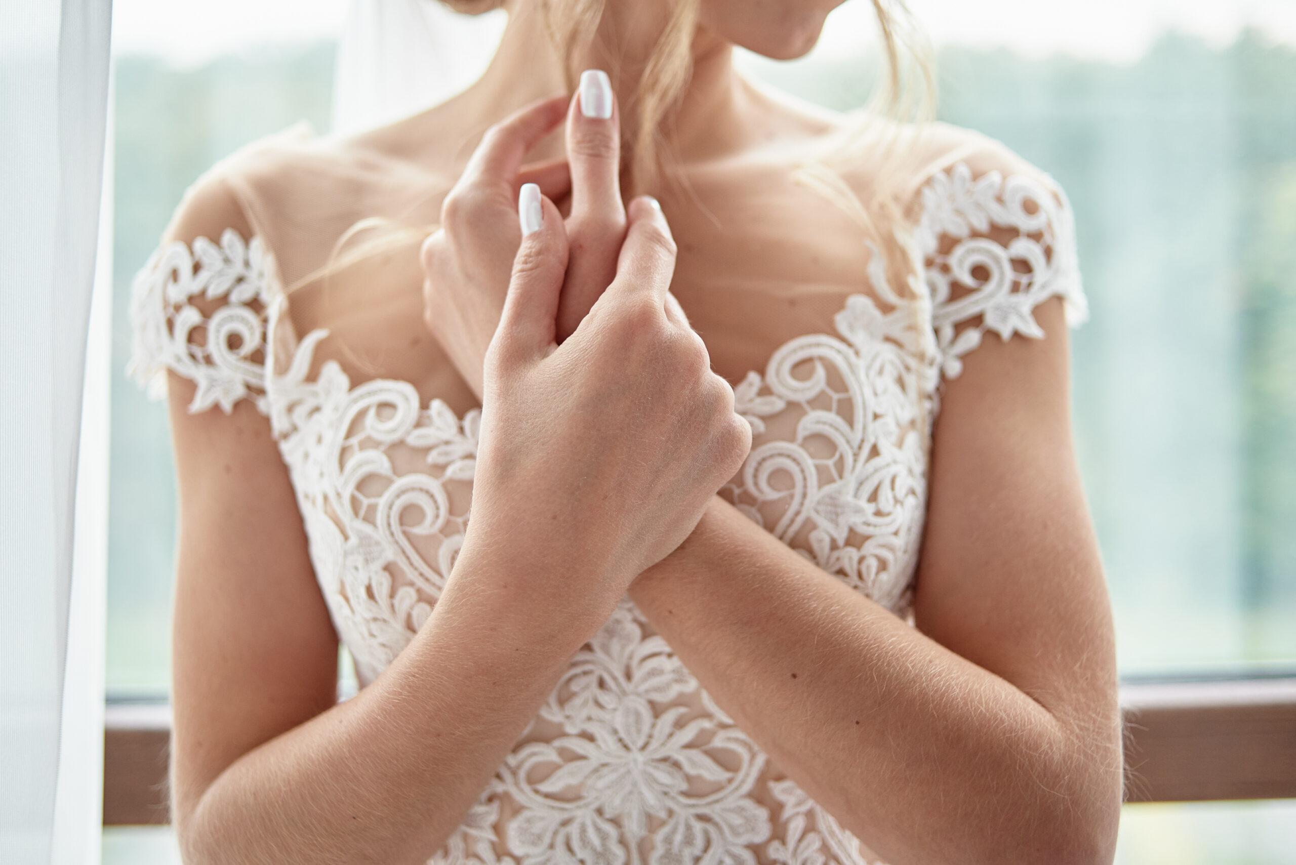 klasyczne paznokcie ślubne w białym kolorze na dłoniach panny młodej