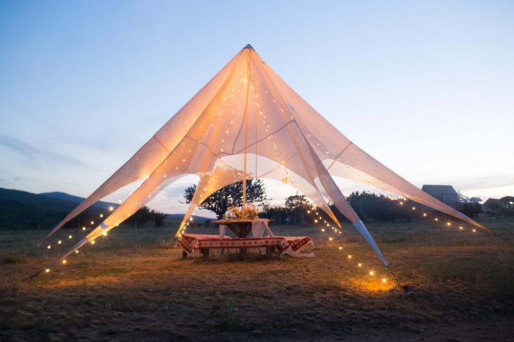 Slow wedding. Namiot weselny w stylu boho oświetlony lampionami.