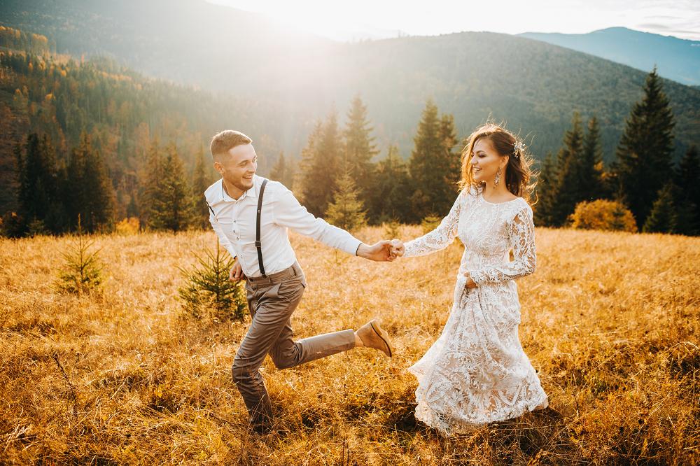 Slow wedding. Para młoda biegnąca przez łąkę w górach.