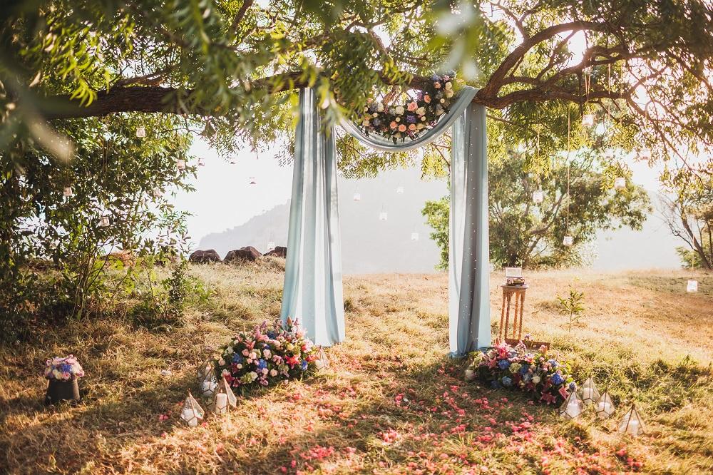 Slow wedding. Piękny ołtarz w stylu boho w lesie na tle zachodzącego słońca.