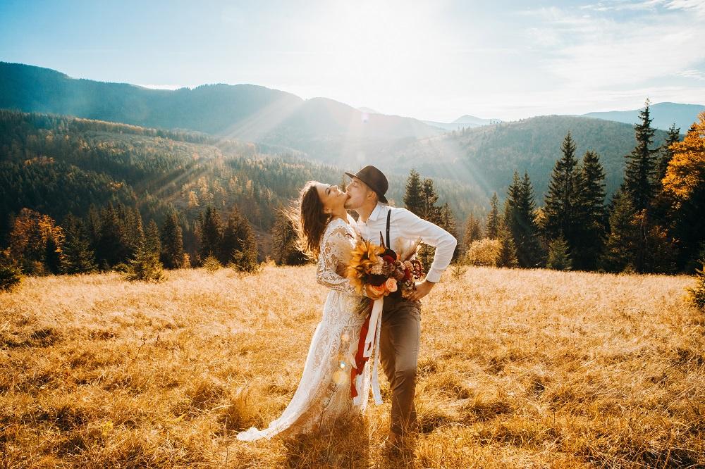 Slow wedding. Stylowa para młoda całujące się na tle zachodu słońca w górach.