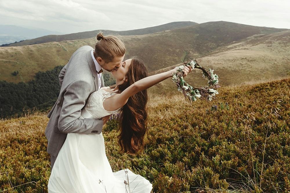 Slow wedding. Panna młoda z winakiem w ręku całuje pana młodego na łące.