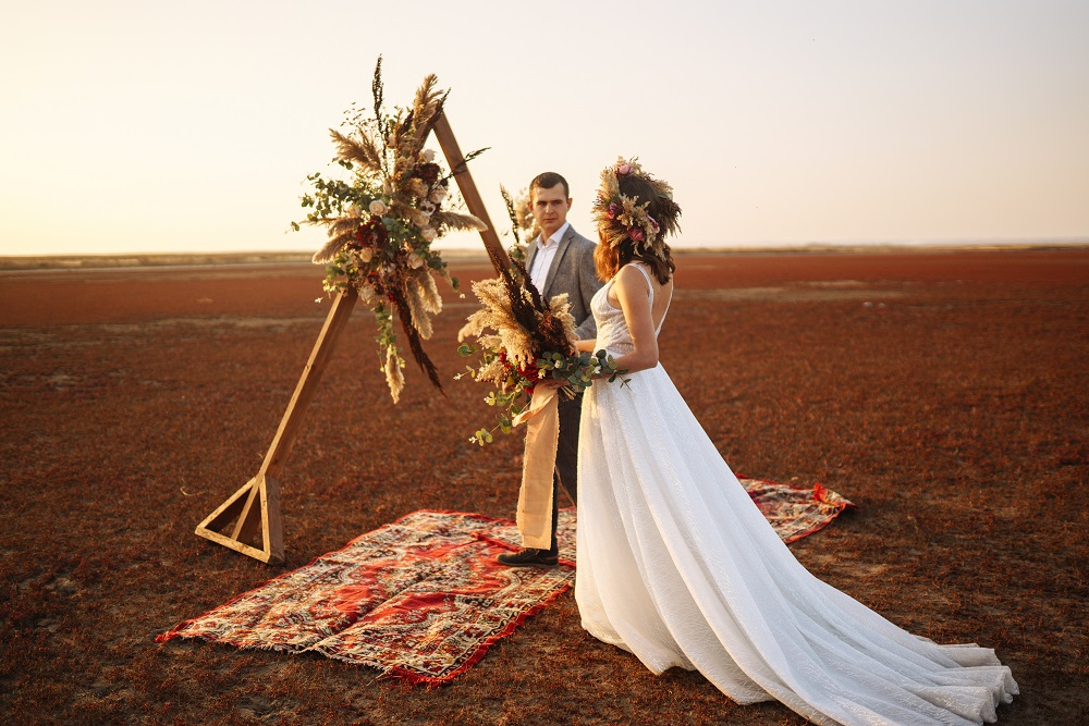 Slow wedding. Piękna para młoda przed ołtarzem w stylu rustykalnym na tle zachodzącego słońca.