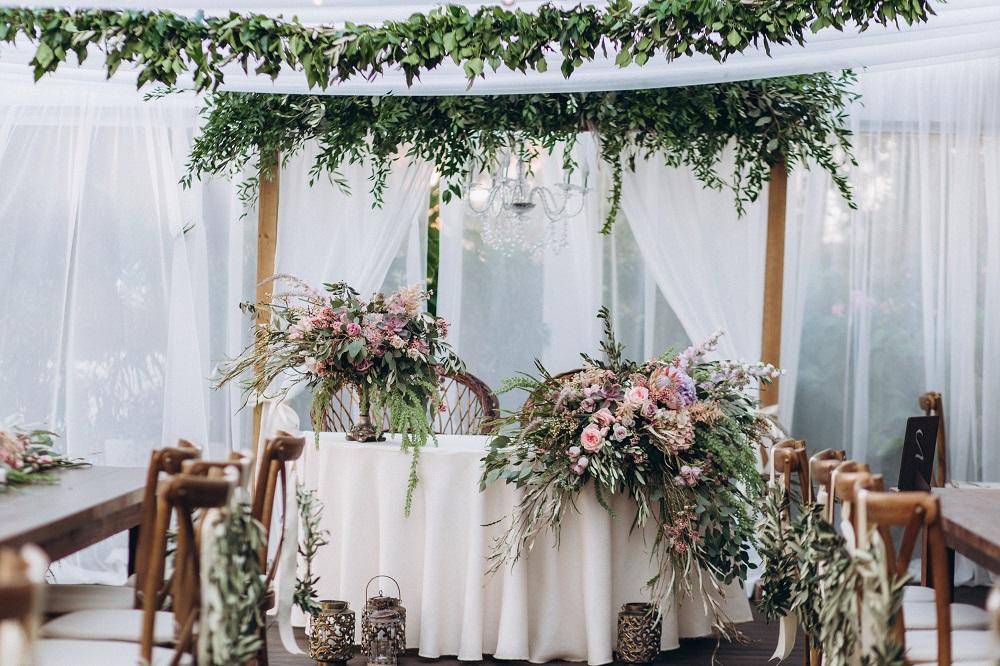 Slow wedding. Stól weselny w stylu boho przystrojony w kwiaty.
