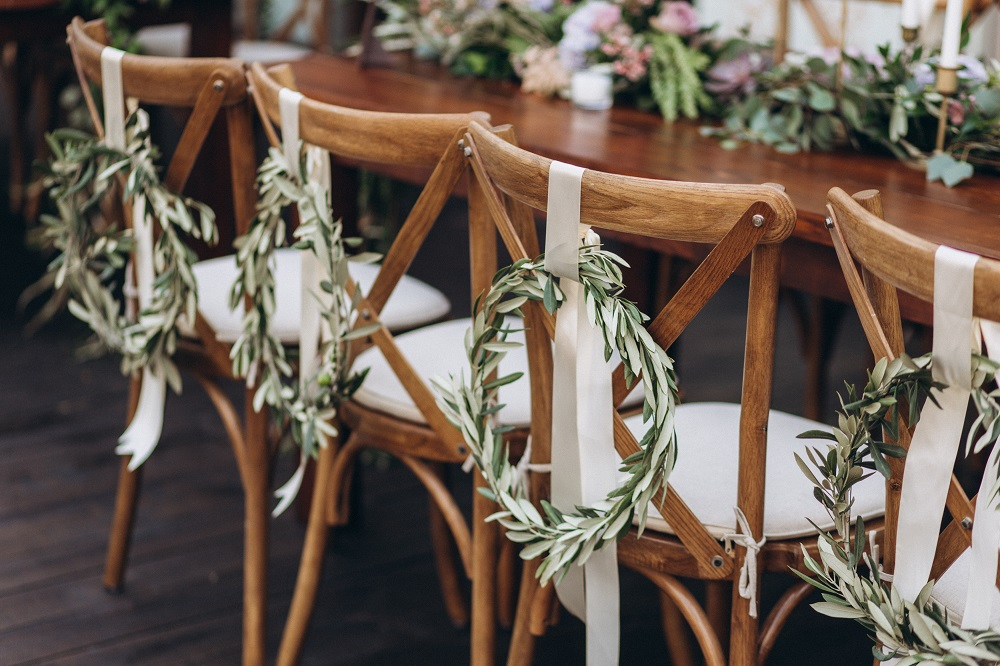 Slow wedding. Stół weselny i krzesła przystrojone wiankami.