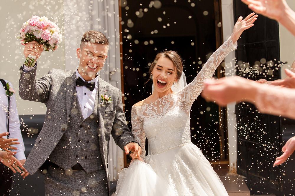 Slow wedding. Uśmiechnięta para młoda wychodząca z kościoła.