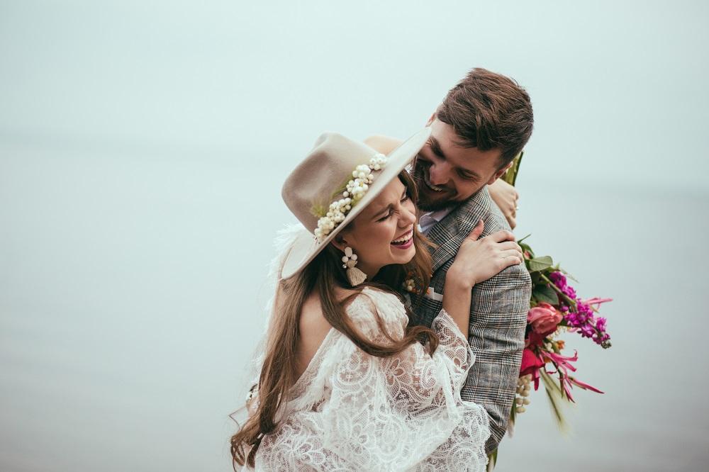 Slow wedding. Uśmiechnięta, stylowa para młoda przytula się.